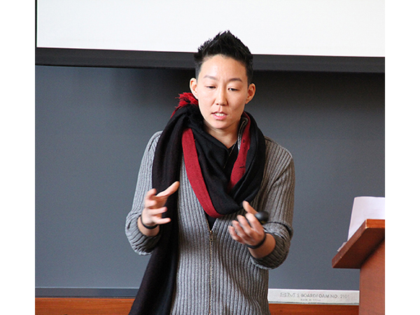Photo of YK gesturing with hands and speaking